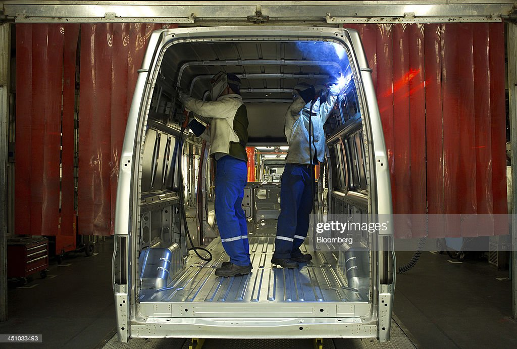 Employees weld joints inside the back of a Ford Transit van as it travels along the production line at the Ford Otosan plant, the joint venture between Ford Motor Co.'s Ford Otomotiv Sanayi AS and Koc Holding AS, in Golcuk, Turkey, on Wednesday, Nov. 20, 2013. Istanbul-based Automobile Distributors' Association, or ODD, forecasts Turkey's total automotive industry market to be between 830k and 870k this year. Photographer: Kerem Uzel/Bloomberg via Getty Images
