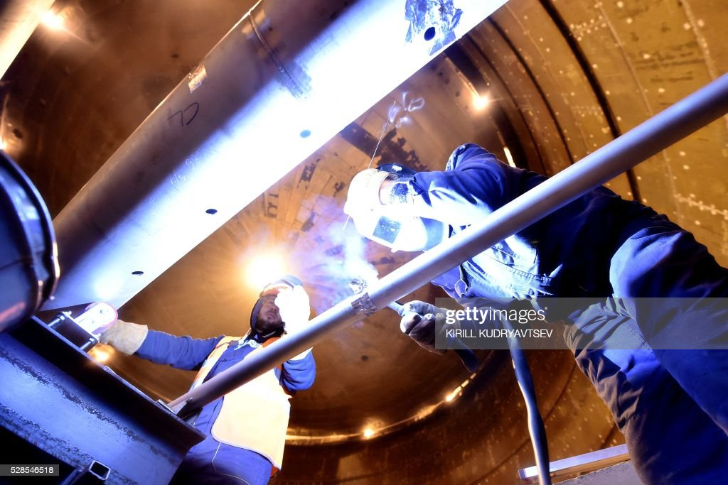 Employees weld pipes inside a natural gas reservoir under for Intranet interior