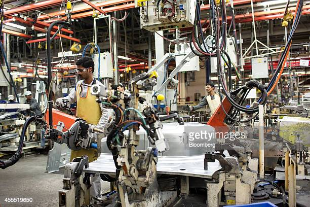 Employees weld the chassis of Volkswagen AG Vento automobiles on the production line at the Volkswagen India Pvt plant in Chakan Maharashtra India on...