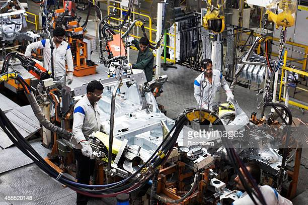 Employees weld the frame and chassis of a Volkswagen AG Vento automobile on the production line at the Volkswagen India Pvt plant in Chakan...