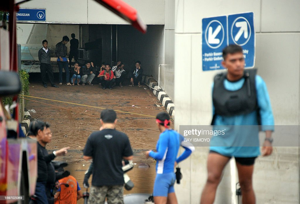 Employees witness the evacuation process for the last victim of a massive flood inside a building's parking lot in downtown Jakarta on January 19, 2013 after three bodies were pulled out of the floodwaters. Floods in Indonesia's capital Jakarta killed 15 people as rescuers found another four bodies, a police spokesman said. AFP PHOTO / Bay ISMOYO