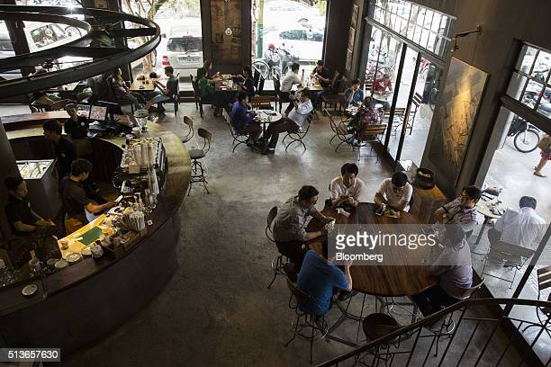 Employees work as customers sit at a coffee shop in Phnom Penh Cambodia on Wednesday March 2 2016 By 2030 more than half of 650 million people in...