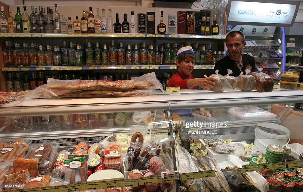 Employees work at a Russian convenience store in the Cypriot capital Nicosia on March 22, 2013. Cyprus plans a tax of up to 15 percent on bank deposits as part of a deal to secure bailout funds, state television said, after Russia spurned its plea for an economic lifeline to stave off bankruptcy.