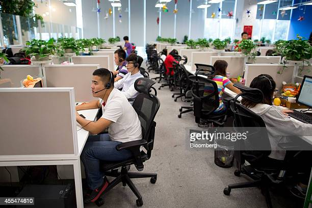 Employees work at computers in the customer support call center section at a Xiaomi Corp office in Beijing China on Friday Sept 12 2014 Xiaomi Chief...