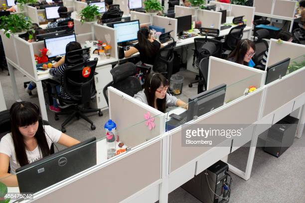 Employees work at computers in the customer support call center at a Xiaomi Corp office in Beijing China on Friday Sept 12 2014 Xiaomi Chief...