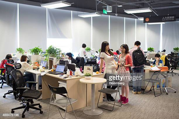 Employees work at laptop computers in an administrative department at the Xiaomi Corp headquarters in Beijing China on Friday Sept 12 2014 Xiaomi...