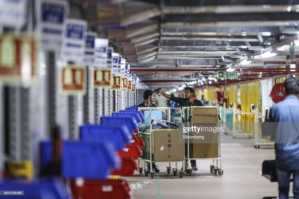 Employees work at the Amazon.com Inc. fulfillment center in Hyderabad, India on Thursday, Sept. 7, 2017. Amazon opened its largest Indian fulfillment center in Hyderabad. The center spans 400,000 square feet with 2.1m cubic feet of storage capacity the company said in a statement. Photographer: Dhiraj Singh/Bloomberg via Getty Images