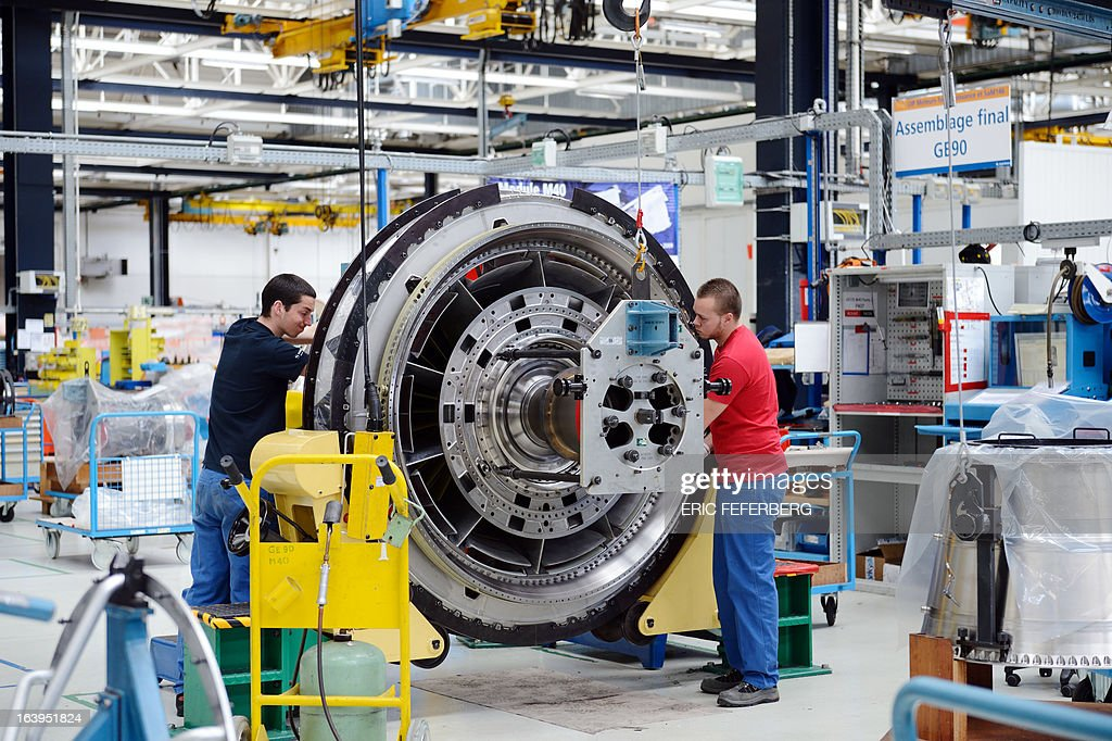 Employees work at the assembly line of French aerospace and defence group Safran, manufacturing engines for commercial and military aircraft, on March 18, 2013 at the SNECMA Villaroche site in Moissy-Cramayel, south east of Paris.