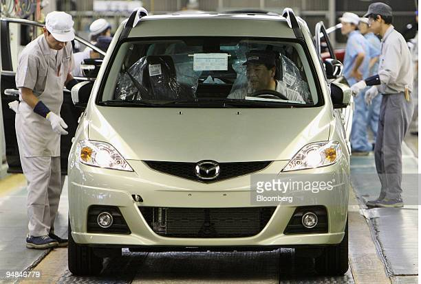 Employees work at the end of the assembly line inside Mazda Motor Corp's Ujina plant in Hiroshima City Japan on Wednesday Sept 16 2008 Mazda Motor...