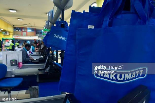 Employees work at the register in a Nakumatt supermarket in Nairobi on July 22 2017 Once a Kenyan success story homegrown Nakumatt supermarkets are...