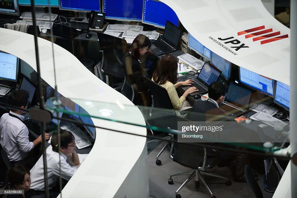 Employees work at the Tokyo Stock Exchange (TSE), operated by Japan Exchange Group Inc. (JPX), in Tokyo, Japan, on Monday, June 27, 2016. The yen was closing in on 99 per dollar at one point Friday and headed for its biggest gain since it was freely floated in February 1973, as Britain's vote to leave the European Union prompted investors to flee global markets and seek safety in Japanese government bonds. Photographer: Akio Kon/Bloomberg via Getty Images