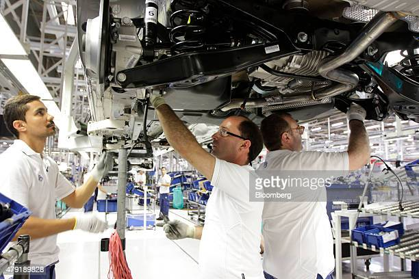 Employees work beneath a Volkswagen Sharan automobile during assembly during manufacture at the Volkswagen AG Autoeuropa car plant in Palmela...