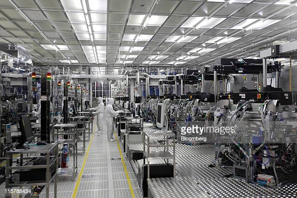 Employees work in a clean room on the production line for 300mm wafers at Renesas Electronics Corp's Naka plant in Hitachinaka city Ibaraki...