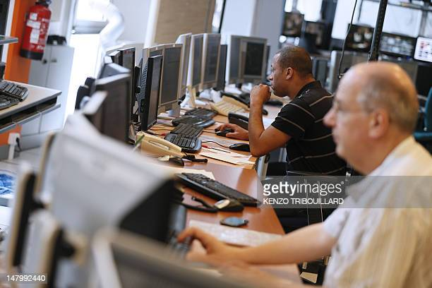 Employees work in a monitoring office at the crisis unit of Europe's biggest Internet provider and third mobile operator France TelecomOrange on July...