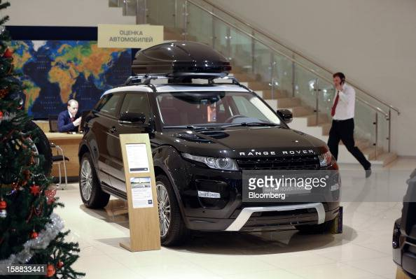 Employees work in a showroom beside a new Range Rover Evoque automobile on display at a Jaguar Land Rover auto dealership in Moscow Russia on...
