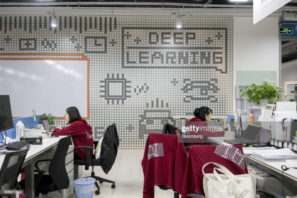 Employees work in front of computers at the Sinovation Ventures headquarters in Beijing, China, on Tuesday, Aug. 15, 2017. Sinovation Ventures' latest growing endeavor, an in-house AI Institute, has about 30 full-time employees with plans to grow headcount to about a hundred within the year. Photographer: Giulia Marchi/Bloomberg via Getty Images
