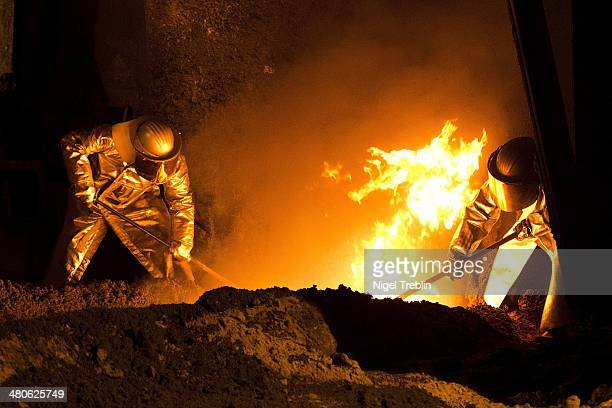 Employees work in front of the blast furnace of German steel manufacturer Salzgitter AG on March 25 2014 in Salzgitter Germany Salzgitter AG is one...