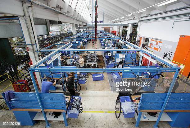 Employees work in the assembly area inside the KTM Fahrrad GmbH bicycle manufacturing facility in Mattighofen Austria on Wednesday April 6 2016...