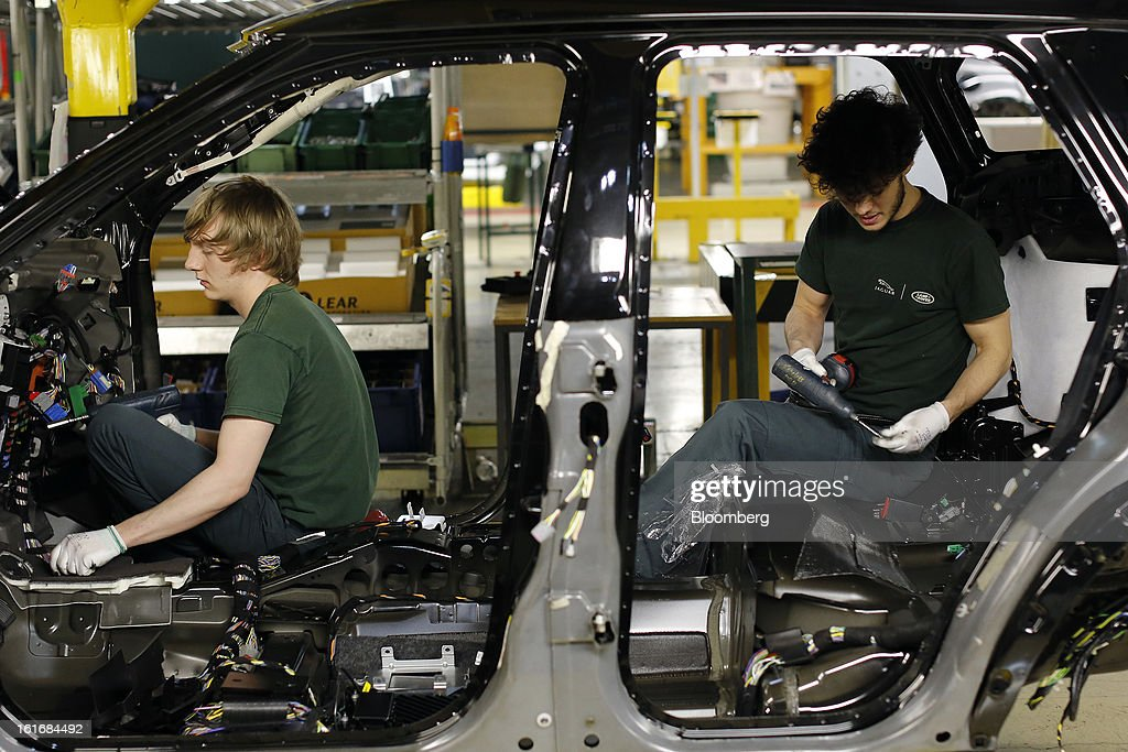 Employees work inside the body shell of a Range Rover Evoque SUV automobile, produced by Jaguar Land Rover Plc, a unit of Tata Motors Ltd., as it travels along the production line at the company's assembly plant in Halewood, U.K., on Wednesday, Feb. 13, 2013. Carmakers from Ford Motor Co. to Audi AG and Jaguar Land Rover Plc are using record amounts of aluminium to replace heavier steel, providing relief to producers of the metal confronting excess supplies and depressed prices. Photographer: Simon Dawson/Bloomberg via Getty Images