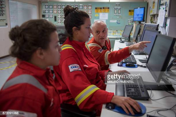 Employees work inside the control room of the Floating Production Storage and Offloading Vessel 'Cidade de Itaguai' oil platform operating at Santos...