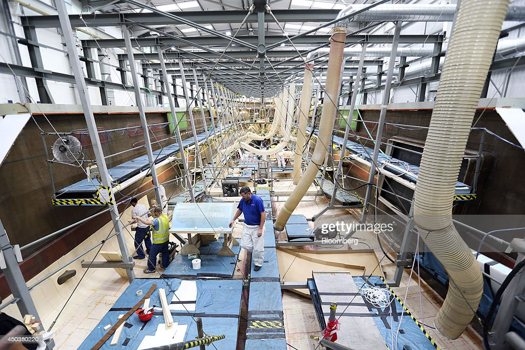 Employees work inside the hull of a 155 Sunseeker yacht produced by Sunseeker International Ltd a unit of China's Dalian Wanda Group during assembly...
