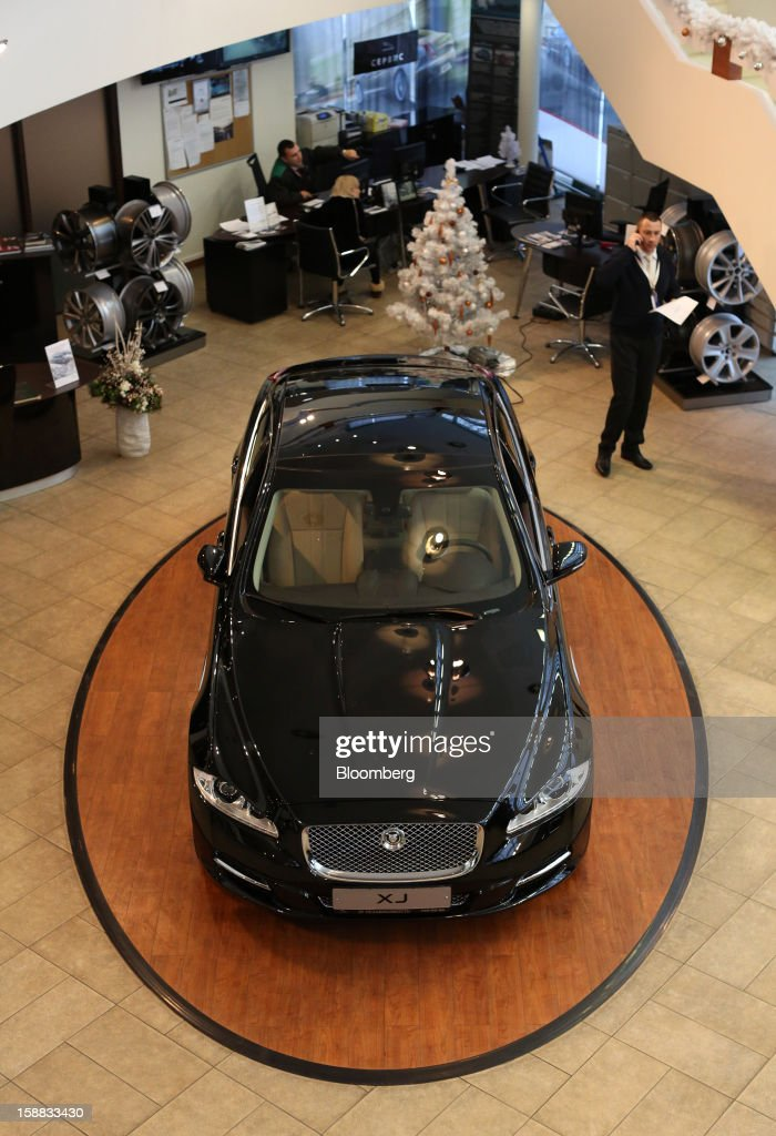 Employees work near a Jaguar XJ series automobile on display in an independent auto showroom in Moscow, Russia, on Friday, Dec. 28, 2012. Tata Motors Ltd.'s Jaguar Land Rover luxury unit signed a letter of intent with Saudi Arabia's government to study the feasibility of setting up a factory to build its models locally. Photographer: Andrey Rudakov/Bloomberg via Getty Images