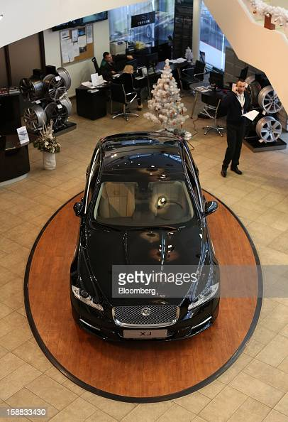 Employees work near a Jaguar XJ series automobile on display in an independent auto showroom in Moscow Russia on Friday Dec 28 2012 Tata Motors Ltd's...