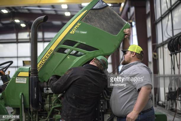 Employees work on a Deere Co John Deere tractor at a United Ag Turf dealership in Waco Texas US on Monday Nov 20 2017 Deere Co is scheduled to...