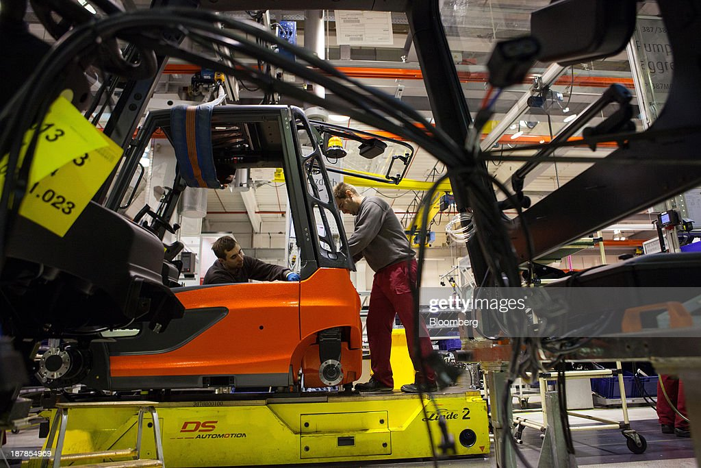 Employees work on a Linde E25 electric forklift truck on the vehicle production line at the Linde Material Handling GmbH factory, a unit of Kion Group AG, in Aschaffenburg, Germany, on Tuesday, Nov. 12, 2013. Kion Group AG, the German forklift-maker which listed shares in June, is looking to expand its global sales network via acquisitions to catch up with main competitor Toyota Industries Corp. Photographer: Krisztian Bocsi/Bloomberg via Getty Images
