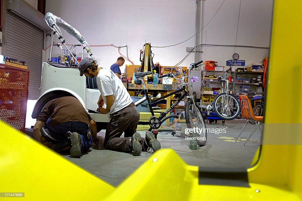 Employees work on a pedicab at the Main Street Pedicabs Inc. manufacturing facility in Broomfield, Colorado, U.S., on Monday, June 24, 2013. The U.S. Census Bureau is scheduled to release durable goods figures on June 25. Photographer: Matthew Staver/Bloomberg via Getty Images
