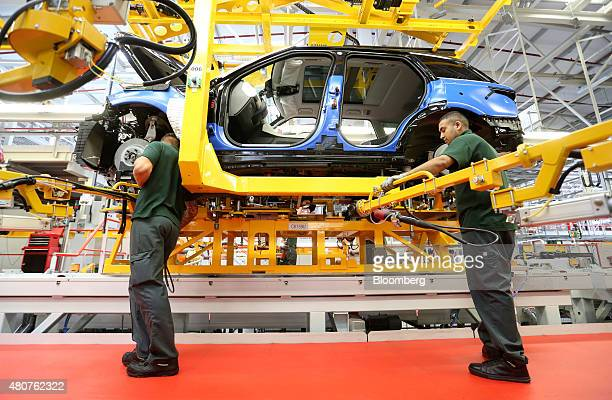 Employees work on a Range Rover Sport SUV using robotic arms at Tata Motors Ltd's Jaguar Land Rover vehicle manufacturing plant in Solihull UK on...