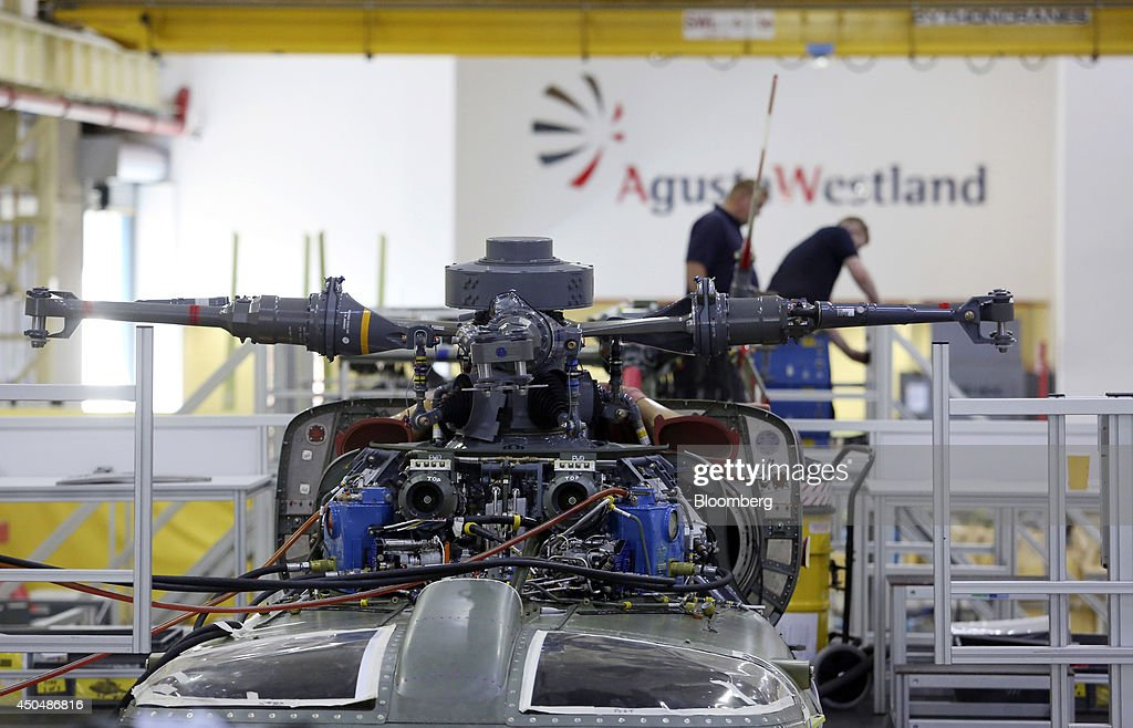Employees work on a Super Lynx 300 helicopter, produced by AgustaWestland, a unit of Finmeccanica SpA, at the company's plant in Yeovil, U.K., on Thursday, June 12, 2014. U.K. unemployment declined more than expected and industrial production rose at the fastest annual pace since 2011, according to reports released this week. Photographer: Chris Ratcliffe/Bloomberg via Getty Images