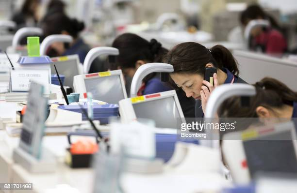 Employees work on a teller line at the Mizuho Bank Ltd branch inside the Mizuho Financial Group Inc headquarters in Tokyo Japan on Friday April 21...