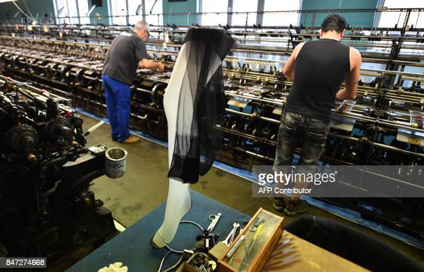 Employees work on a weaving loom in the factory of silk stockings and underwear manufacture company Arsoie Cervin on September 7 2017 in Sumene...