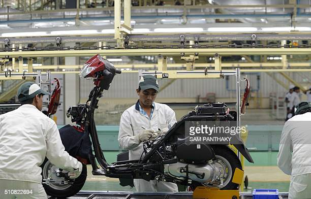 Employees work on an assembly line of Activa scooters at the new plant of Honda Motorcycle and Scooter India Pvt Ltd in Vithalapur some 80 km from...
