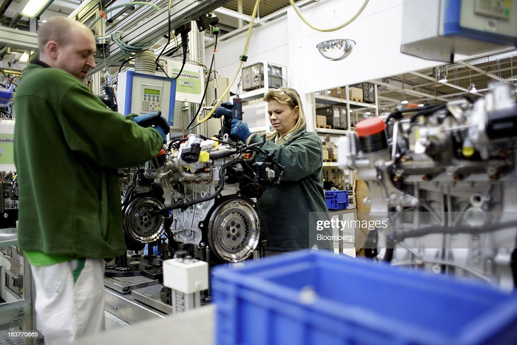 Employees work on an engine assembly on the automobile production line at Skoda Autos AS in Mlada Boleslav, Czech Republic, on Friday, March 15, 2013. VW, which also owns the Porsche luxury-auto brand as well as the Skoda and Seat volume marques, will build at least 10 plants globally, including seven in China, Martin Winterkorn, chief executive officer of Volkswagen AG, said. Photographer: Martin Divisek/Bloomberg via Getty Images