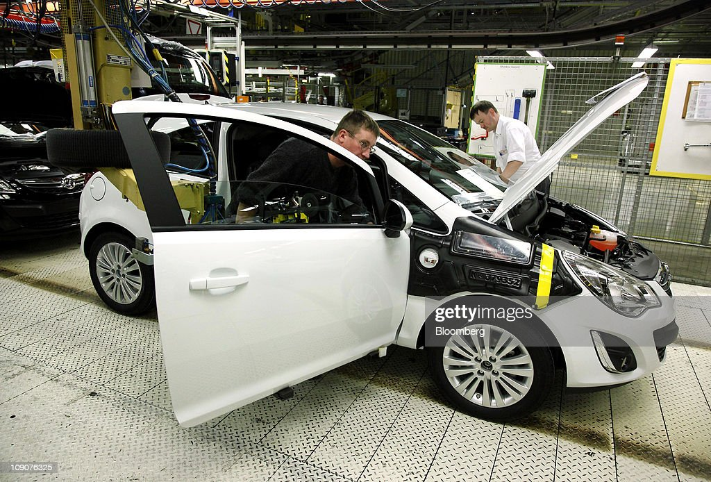 Employees work on an Opel Corsa automobile as it passes along the production line at the General Motor Co.'s Adam Opel plant in Eisenach, Germany, on Friday, Feb.11, 2011. General Motors Co.'s Opel unit may break even this year, excluding restructuring costs, said Nick Reilly, GM's European chief. Photographer: Jochen Eckel/Bloomberg via Getty Images