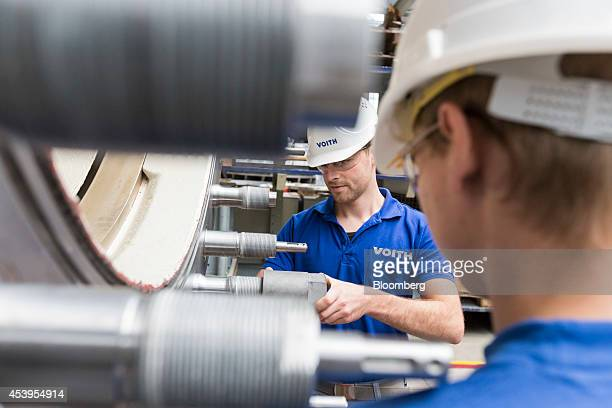 Employees work on assembly of the spherical valve of a hydropower plant in the workshop at the Voith GmbH factory in Heidenheim Germany on Thursday...