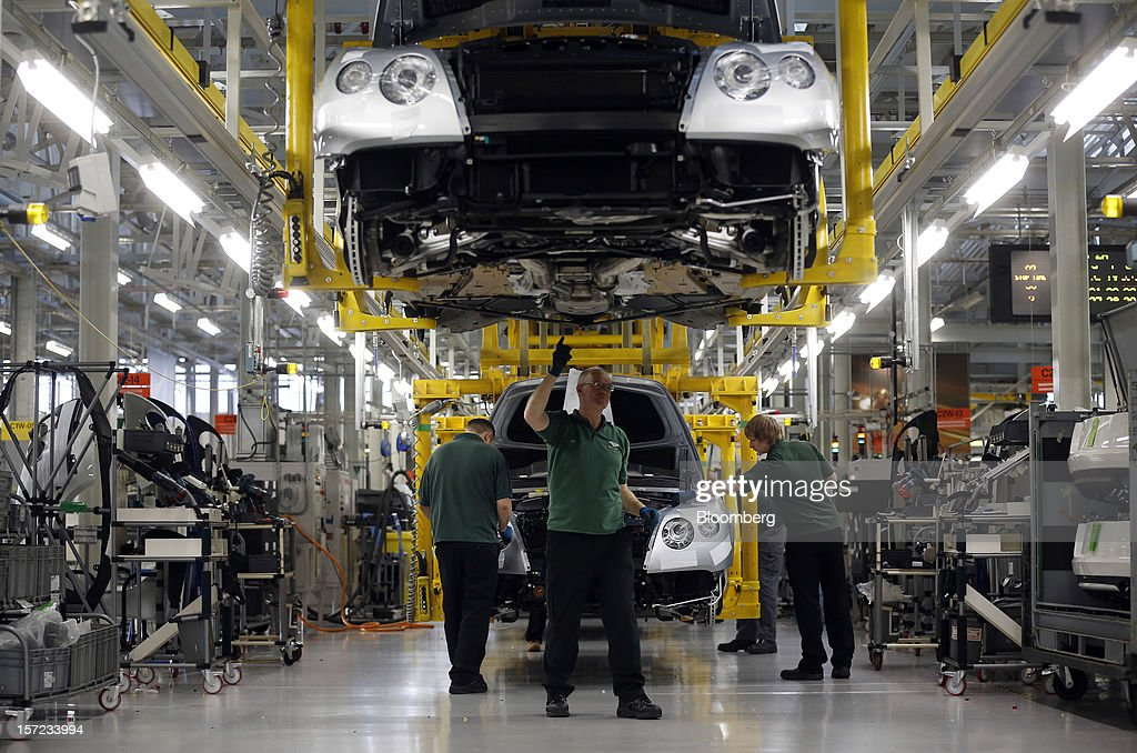 Employees work on Bentley Continental automobiles as they travel along the production line inside the Bentley Motors Ltd. workshop in Crewe, U.K., on Thursday, Nov. 29, 2012. Consumer spending and exports propelled the U.K. economy to its fastest growth since 2007 in the third quarter as the Olympics and a post-Jubilee rebound saw household expenditure rise the most in more than two years. Photographer: Simon Dawson/Bloomberg via Getty Images