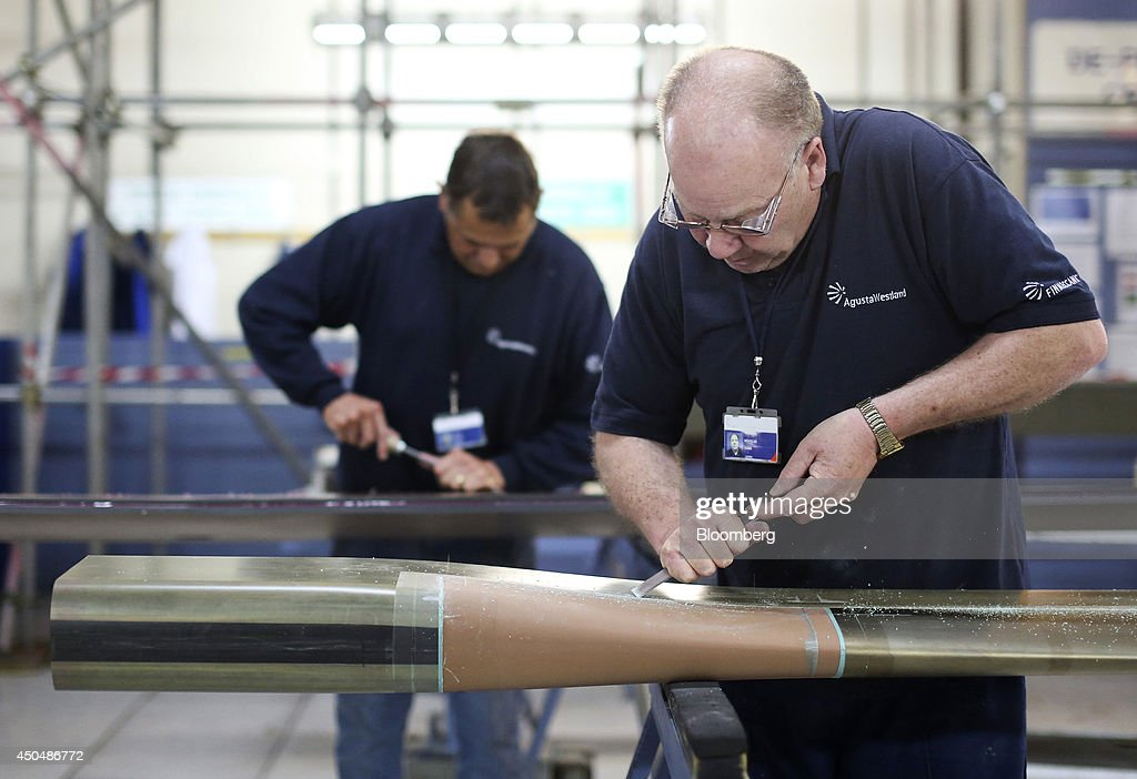 Employees work on blades for helicopters produced by AgustaWestland, a unit of Finmeccanica SpA, at the company's plant in Yeovil, U.K., on Thursday, June 12, 2014. U.K. unemployment declined more than expected and industrial production rose at the fastest annual pace since 2011, according to reports released this week. Photographer: Chris Ratcliffe/Bloomberg via Getty Images