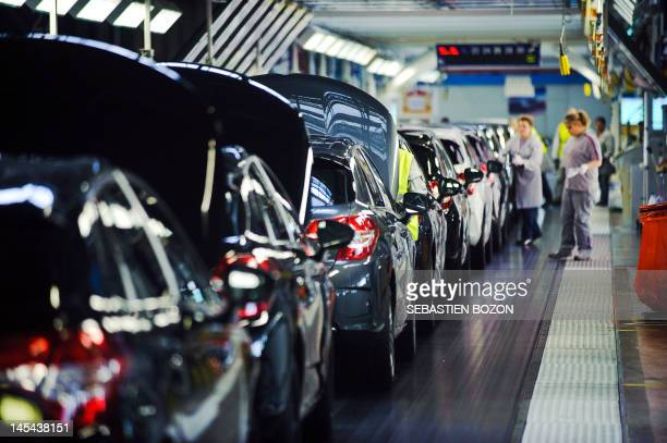Employees work on citroen c4 and DS4 production lines of the French car maker PSA Peugeot Citroen on April 13 2012 during a special day visit for DS4...