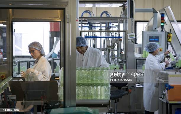 Employees work on cosmetic products on a production line at the plant of French multinational pharmaceutical and cosmetics company 'Pierre Fabre' in...