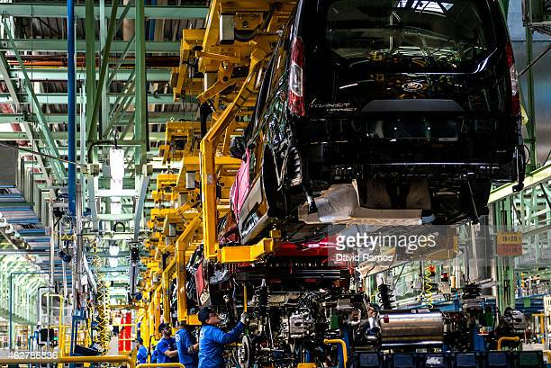 Employees work on Ford Mondeo vehicles on the production line during assembly at Ford plant in Almussafes on February 5 2015 in Valencia Spain The...