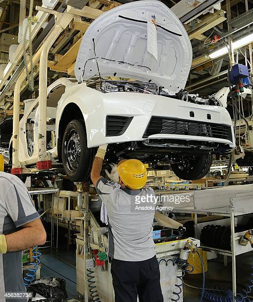 Employees work on incomplete vehicles move along the production line at the Toyota Motor Manufacturing Turkey's assembly plant in Sakarya Turkey on...