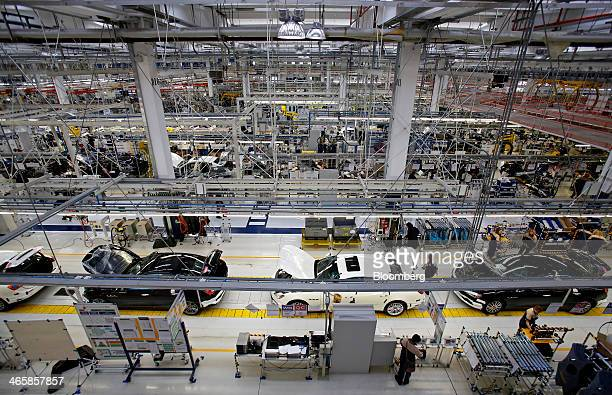 Employees work on Maserati Ghibli luxury automobiles produced by Maserati SpA as they travel along the semiautomated production line at Fiat SpA's...