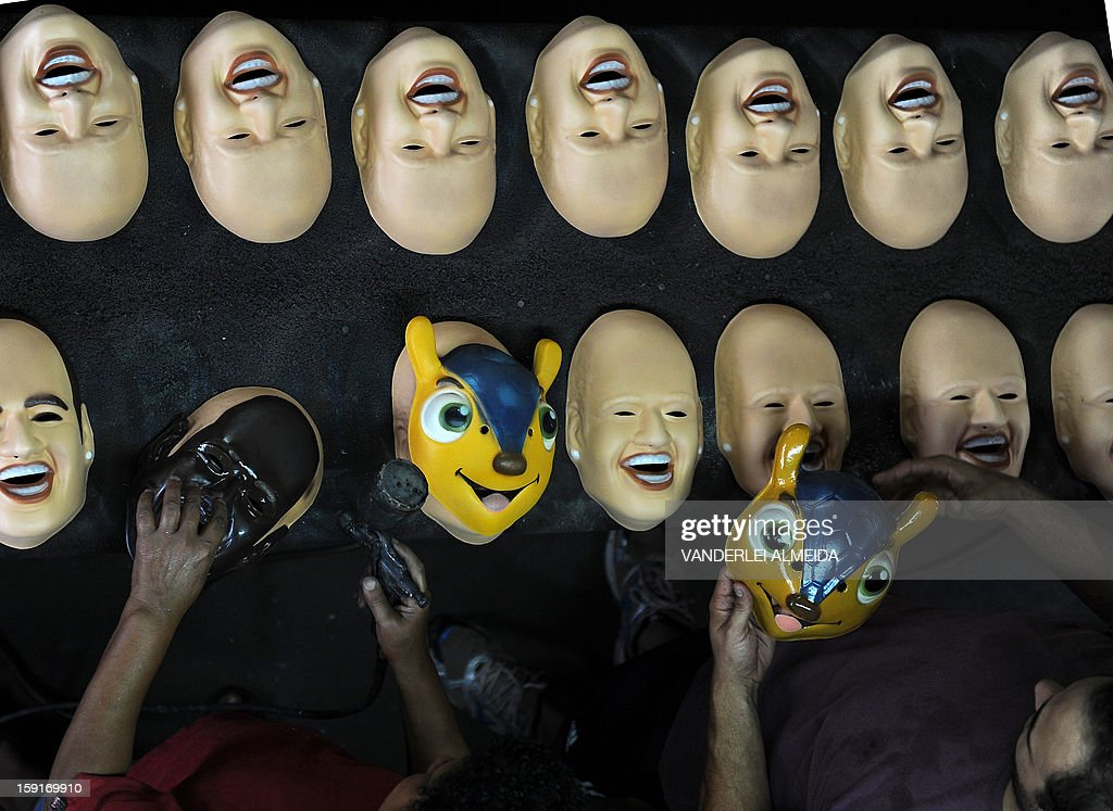 Employees work on masks of Brazilian football star Neymar, the president of the Brazilian Supreme Court Joaquim Barbosa and the mascot of the Brazil 2014 FIFA World Cup, 'Tatu Bola-Fuleco', at the carnival masks factory Condal, in Sao Gonçalo, about 35 km from downtown Rio de Janeiro, on January 9, 2013. Rio's world famous carnival takes place February 9-12. AFP PHOTO/VANDERLEI ALMEIDA