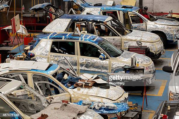 Employees work on reinforcing vehicles at Ballistic Protection Co's armored car workshop in Mexico City Mexico on Tuesday April 29 2014 Mexico's...