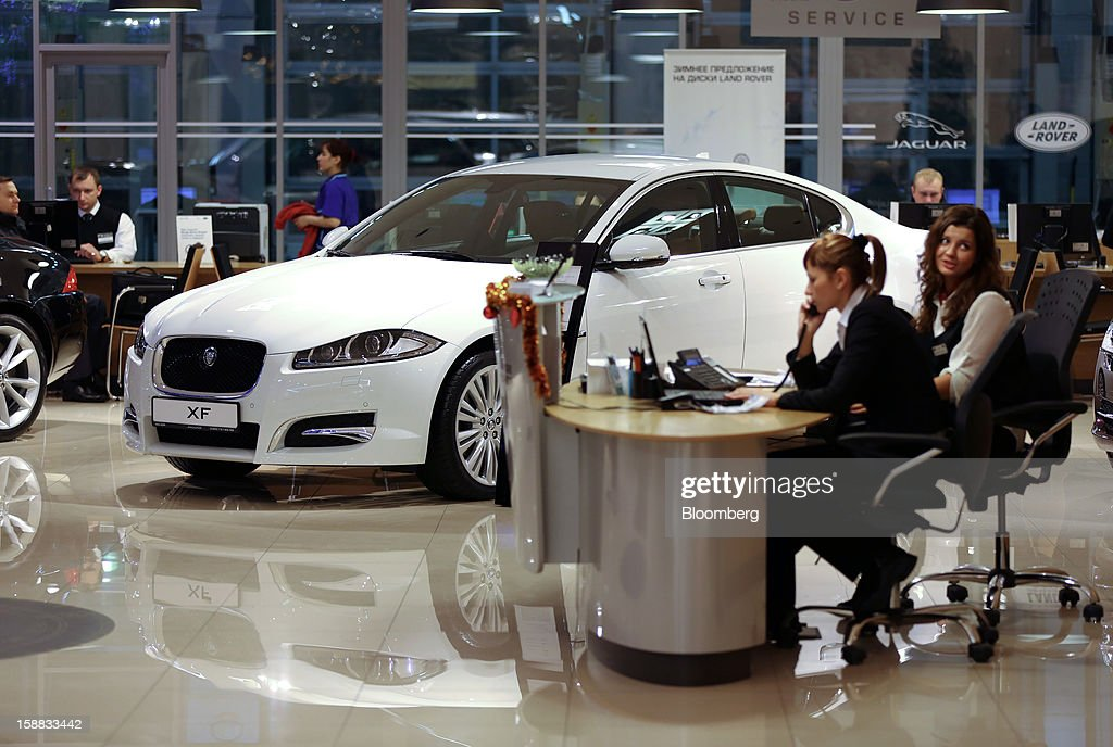Employees work on telephones at a service desk near a Jaguar XF automobile inside a Jaguar Land Rover auto dealership in Moscow, Russia, on Thursday, Dec. 27, 2012. Tata Motors Ltd.'s Jaguar Land Rover luxury unit signed a letter of intent with Saudi Arabia's government to study the feasibility of setting up a factory to build its models locally. Photographer: Andrey Rudakov/Bloomberg via Getty Images