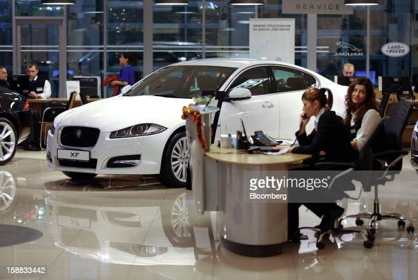 Employees work on telephones at a service desk near a Jaguar XF automobile inside a Jaguar Land Rover auto dealership in Moscow Russia on Thursday...