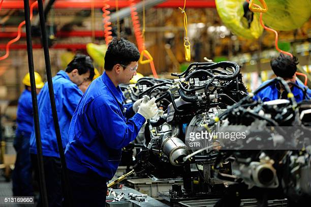 Employees work on the assembly line of a car factory in Qingdao eastern China's Shandong province on March 1 2016 Manufacturing activity in China...